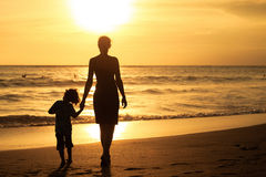 Mother and son playing on the beach at the sunset time. Stock Photos