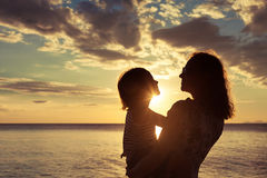 Mother and son playing on the beach at the sunset time. Stock Images