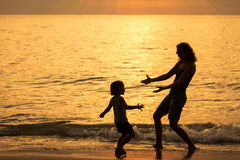 Mother and son playing on the beach at the sunset time. Stock Image