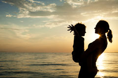 Mother and son playing on the beach at the sunset time. Royalty Free Stock Photography