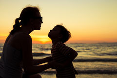 Mother and son playing on the beach at the sunset time. Royalty Free Stock Image