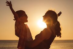 Mother and son playing on the beach at the sunset time royalty free stock photography