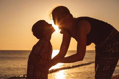 Mother and son playing on the beach at the sunset time royalty free stock images