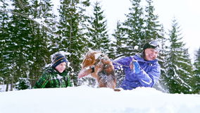 Mother and son playing with beagle dog in deep snow stock footage
