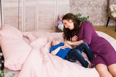 Little boy smiling and playing with his mom in the bed. Mother and son playing in a bedroom. Little boy smiling and playing with his mom in the bed. Modern royalty free stock images