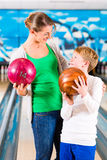 Mother and son playing at bowling center Stock Photos