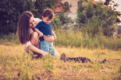 Mother and son playing with cat. In the grass field Stock Image