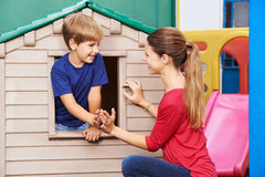 Mother and son playing clapping game in nursery. Happy mother and son playing a clapping game in nursery at home stock image