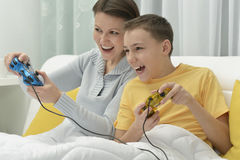 Mother and son playing computer game. Young mother and son playing computer game in bed Stock Image
