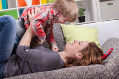 Mother and son playing on the couch Stock Images