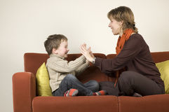 Mother And Son Playing On A Couch Stock Photos