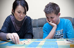 Mother and son playing dice. Mother and teenage son playing dice game at home Stock Images
