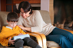 Mother and son playing on digital tablet PC Royalty Free Stock Photo