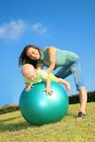 Mother and son playing on a fitness ball. Beautiful young mother playing with her baby in fitness ball on the green grass and the blue sky Royalty Free Stock Photography