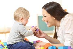 Mother and son playing on the floor. Side view of a happy mother and son playing with toys on the floor Stock Photography