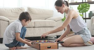 Mother and son playing foosball at home. Cheerful mother with her son playing foosball game at home stock video footage