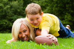 Mother and son playing football outdoors