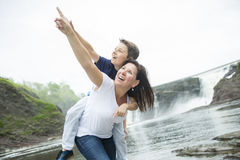 Mother and son playing in front of a waterfall. A mother and son playing in front of a waterfall Stock Photography