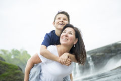 Mother and son playing in front of a waterfall. A mother and son playing in front of a waterfall Stock Image