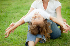 Mother and son playing on the grass at the day time. Royalty Free Stock Photo