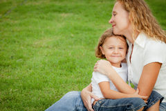 Mother and son playing on the grass at the day time. Royalty Free Stock Photography