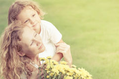 Mother and son playing on the grass at the day time. Mother and son playing with flowers on the grass at the day time. Concept of friendly family Stock Images
