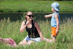 Mother and son playing with grass on the meadow. Happy mother and little son playing with grass on the meadow on the bank of a small river. Family fun outdoor royalty free stock photo