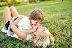 Mother and son are playing hugging on the grass in the park. Mothers Day Stock Photo