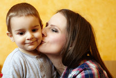 Mother and son playing. Mother kissing her little boy on the cheek, indoors Royalty Free Stock Images