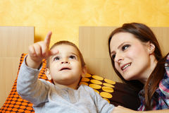Mother and son playing. Little boy showing to his mother something on the ceiling Royalty Free Stock Photography
