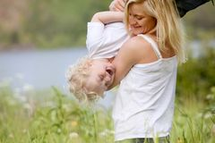 Mother and Son Playing in Meadow. A mother tickling and playing with excited happy son in a green meadow stock photography