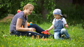 Mother and son playing outdoor on the green lawn Royalty Free Stock Photo