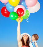 Mother with son playing outdoors. Portrait of a happy mother with little adorable son holding many colorful balloons over blue sky background, with pleasure Stock Image