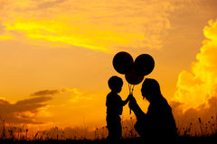 Mother and son playing outdoors at sunset silhouette Stock Photos