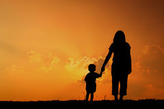 A mother and son playing outdoors at sunset silhouette. Silhouette of a mother and son playing outdoors at sunset Stock Photo