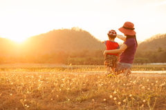 A mother and son playing outdoors at sunset. Silhouette Royalty Free Stock Image