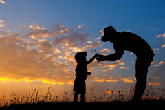 A mother and son playing outdoors at sunset silhouette Stock Photography
