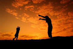 A mother and son playing outdoors at sunset silhouette Stock Photo