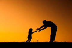 A mother and son playing outdoors at sunset silhouette Stock Photos