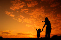 Mother and son playing outdoors at sunset silhouette Royalty Free Stock Photo