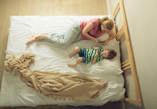 Mother and son playing with phones. Mother with her son lying on the bed with the phone in his hand Royalty Free Stock Photography