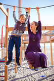 Mother and son playing at playground. A mother and son playing on ropes at a playground at the beach during summer Royalty Free Stock Image