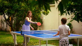Mother and son playing table tennis. Young mother and son playing table tennis outdoors in the hotel stock video