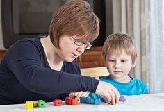 Mother and son playing together. Mother and her little son playing colorful toys at home Stock Photo