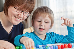 Mother and son playing together. Mother and her little son playing colorful toys at home Royalty Free Stock Photos