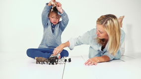 Mother and son playing together with different plastic toy animals stock video