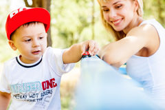 Mother and son playing. Together outdoors in park with soap bubbles Royalty Free Stock Image