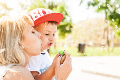 Mother and son playing. Together outdoors in park with soap bubbles Royalty Free Stock Photos