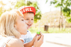 Mother and son playing. Together outdoors in park with soap bubbles Royalty Free Stock Images