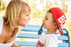 Mother and son playing. Together outdoors in park with soap bubbles Stock Photo
